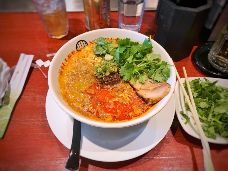 Photo Description: Killer Noodles bowl of tantanmen. It is a white bowl with the contrasting soup base that looks orangish red, cilantro, a dollop of a brown looking thing in the middle with a side of more cilantro.