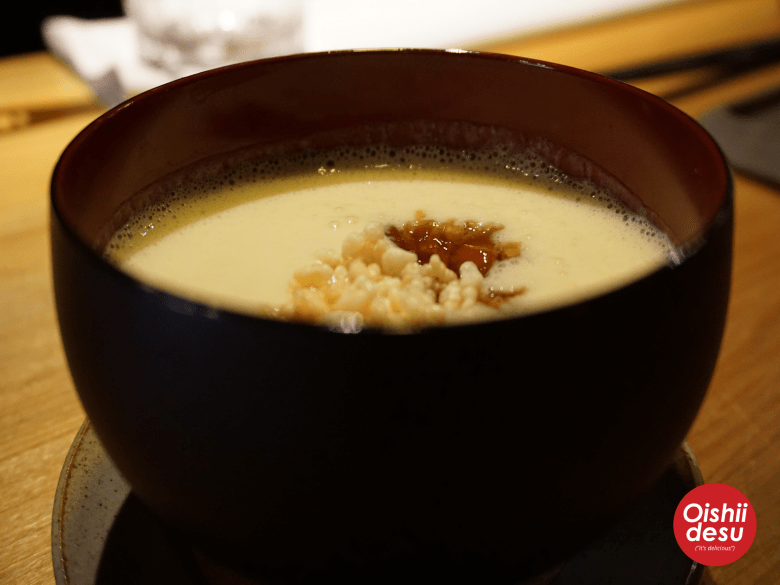 """Photo Descriptions: the first dish was a chilled corn soup with yubs tofu skin and puffed rice. It came in a black """"miso soup"""" style bowl and the puffedd rice was placed in the middle of the soup."""