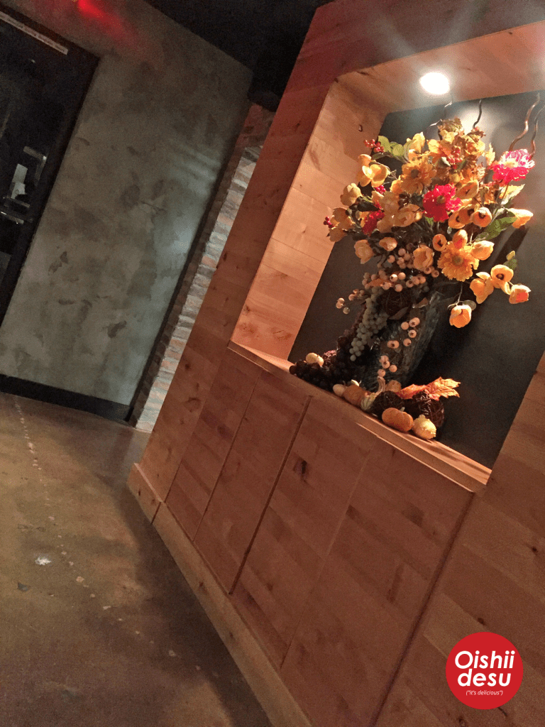 Photo Description: there's a wall enclave with a vase with a seasonal flowers.