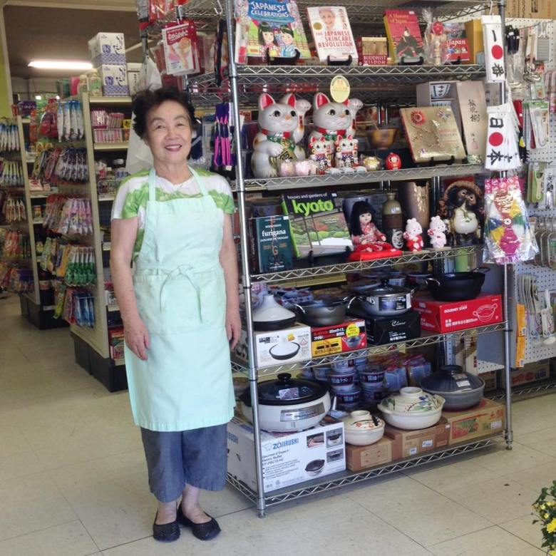 Photo Description: the owner of Sage Market posing inside of the store next to a shelf full of products from maneki neko to donabe.