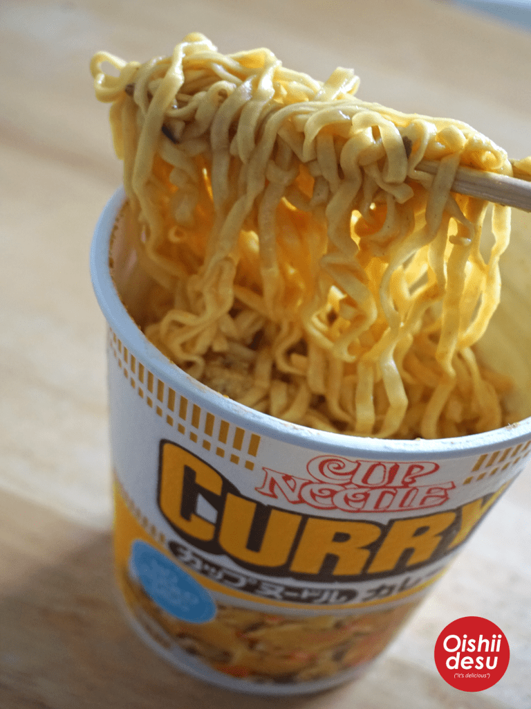 Photo Description: golden strands of rectanglish noodles that are crinkly in look fill this cup.