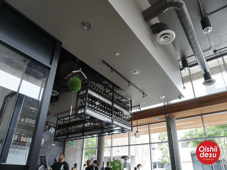 Photo Description: the semi exposed ceiling shows the HVAC and the bar area with all their bottles of something... most likely sake?