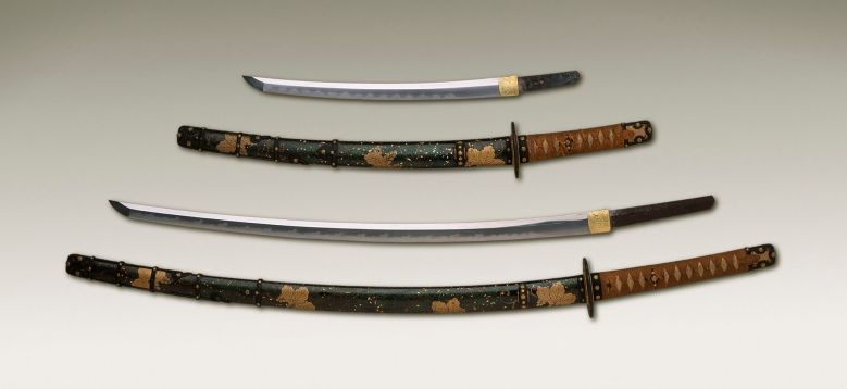 Photo Description: Japanese samurai sword. 4 blades shown, two unsheathed, and two sheathed. The sheathed blades have very ornate floral motif in gold and black.