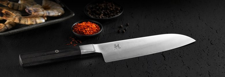 Photo Description: a shot of the German Japanese Zwilling Miyabi knife. It is set on a black textured surface that looks like stucco. In the background are two small bowls of red chili, sichuan peppercorns, and some raw shrimp which are all Chinese food ingredients.