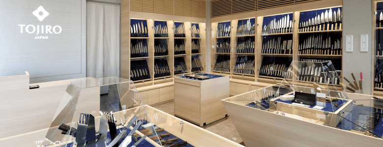 Photo Description: the showroom of Tojiro's showroom. The room is very nicely lit, the showcases are a light wood color with glass partitions for the cases. The knives are set on a blue background with all the knives are vertically positioned side by side to each other. In the upper left corner is a light grey wall with Tojiro Japan in white.