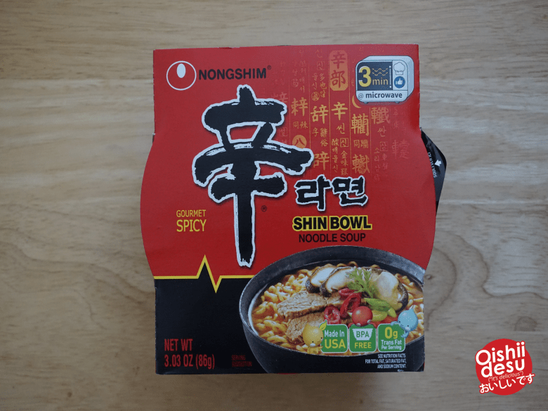 "Photo Description: this is the Nongshim packaging of the Shin Bowl Noodle Soup. The packaging has an outer cardboard sleeve that is primarily RED and black with yellow highlights. On the packaging it says ""3 min"" high for microwave."