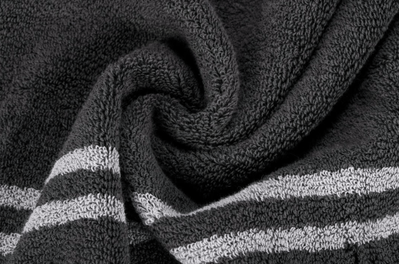 Photo Description: a close-up shot of Mizu Towels. The pic shows a blackish colored towel with a two white strips that are parallel to each other.