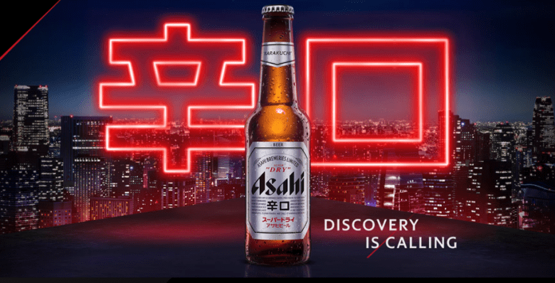 """Photo Description: Asahi Beer bottle set against a night time city skyline with a red neon Japanese kana with the word """"Asahi."""" in English """"discovery is calling."""""""