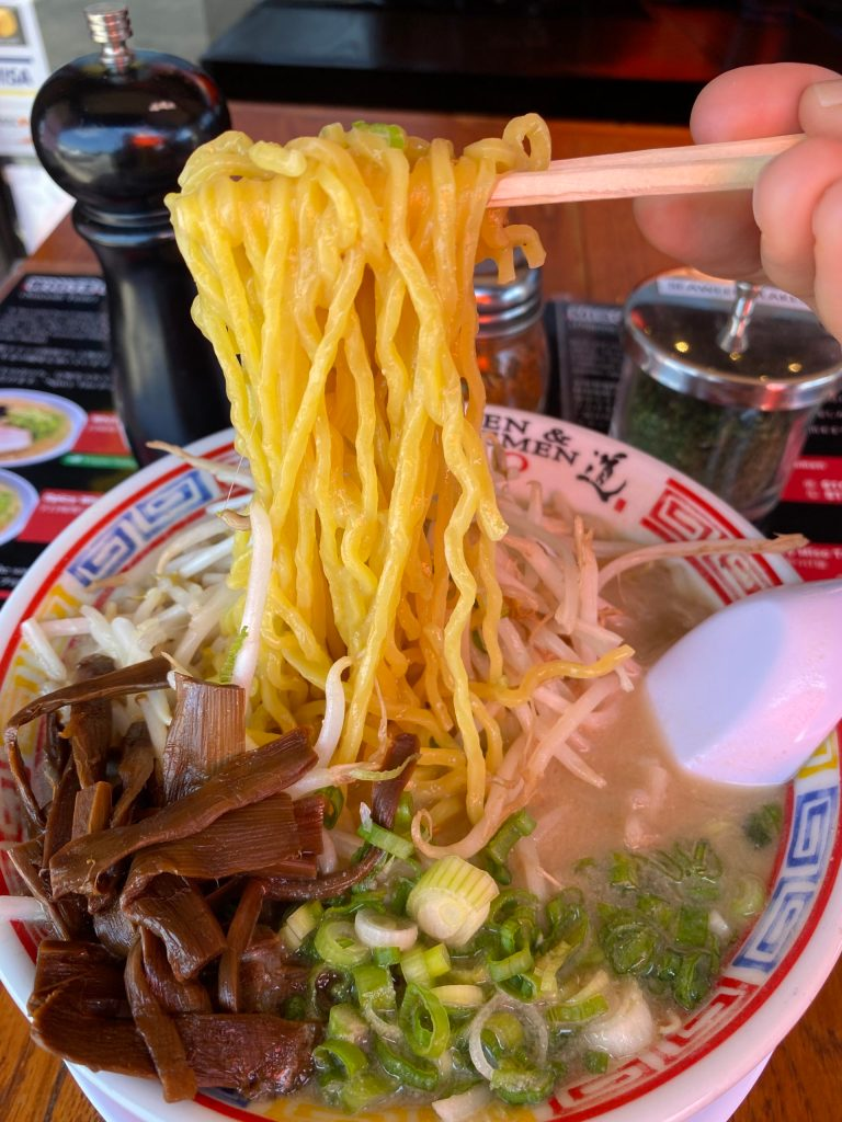 Photo Description: Zac with his chopsticks is holding up a long pull of ramen noodles above his bowl of ramen at Tsukemen & Ramen Tao. The bowl is filled with a dark menma, green onion, and moyashi in a light tonkotsu colored broth.