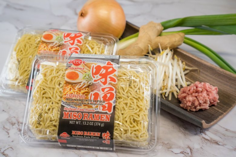 Photo Description: a pic of Miso Ramen which depicts the packaging of Sun Noodles. In the pic, two packages of noodles are seen with tamanegi, tokyo negi, moyashi, ginger, and minced pork in the background.