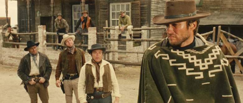 Photo Description: Clint Eastwood in Fistful of Dollars with 3 cowboys sitting on a fence, while 3 others are standing directly behind him.