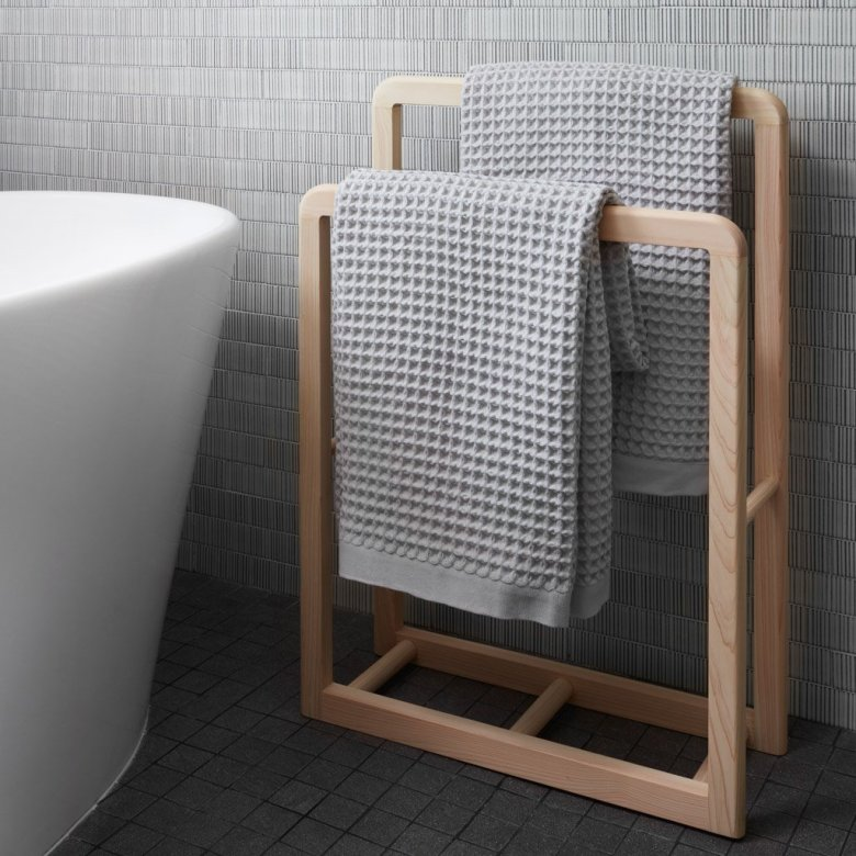 Photo Description: a product shot of the Imabari waffle towel set that is crafted in Japan. The very light greyish towels are set on a light wood colored towel rack hung horizontally across. Also in the shot is a very large white tub (all modern looking).