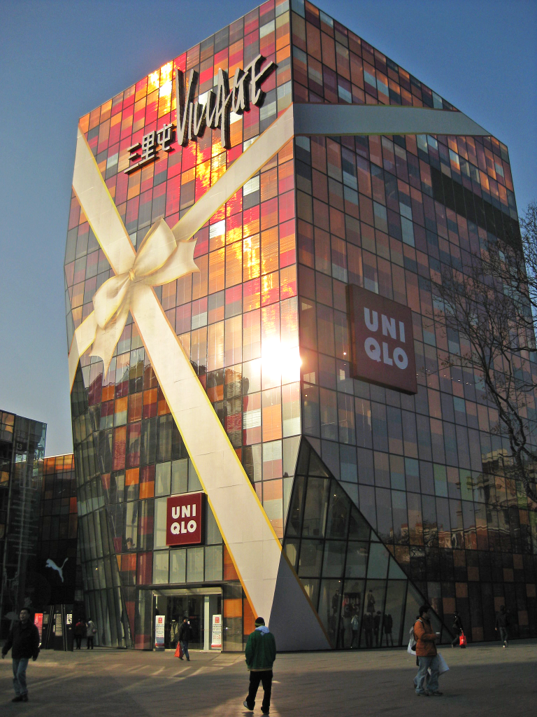 Photo Description: Uniqlo in Beijing China. The building a multi-colored square grid of orange, red, yellow/gold, to dark greys covering the entirety of the building square mutli-story building.