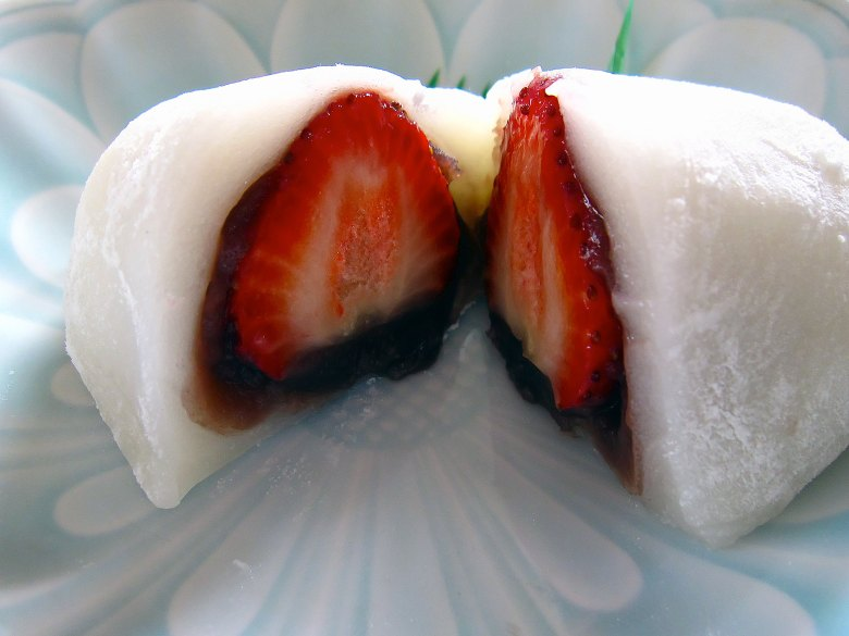 Photo Description: strawberry mochi with sweet red bean (adzuki) and a fresh strawberry in the middle. The pic, is of one cut in half where you can see a cross-section which shows the mochi layer, red bean paste, and the strawberry.