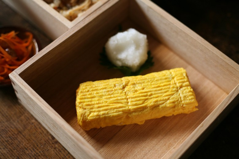 Photo Description: a beautifully taken pic of a most likely a cedar box used as serving containers. In one is nicely prepared tamagoyaki with what looks like a mound of grated daikon?