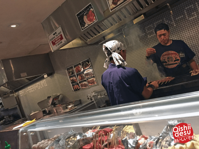 Photo Description: two of the grill guys at Shin Sen Gumi yakitori in Fountain Valley, California. One is seasoning the yakitori on the grill (real Japanese yakitori grill), while the other is flipping and rotating the skewers on the grill. In the foreground, is a cooler with several skewers in it.