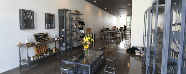 Photo Description: a narrow retail space has white walls, a somewhat glossy dark floor with a battleship grey looking display cases. The enclosed cases contain several knives. The rest of the furniture looks the same although there is one wall side table with an antique look to it.