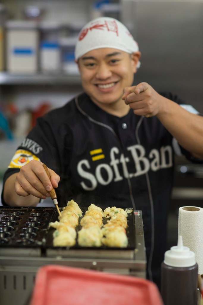 Photo Description: Karl cooking on the takoyaki grill. He's wearing a SoftBank jersey.