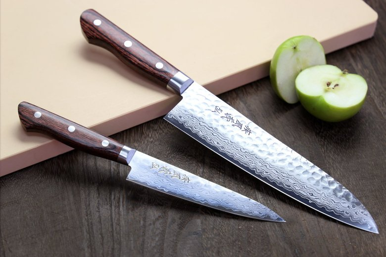 Photo Description: Yoshihiro knives (2) displayed. Both are Damascus with brown handles. On the right-hand side is a green apple cut in half.