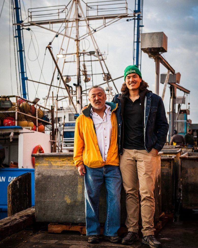Photo Description: Rex (pops) and Blake Ito are standing on the deck of fishing boat on a pier.