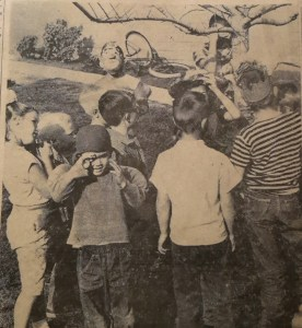 COMPLETE WITH A STRONG MAN, clowns, tight rope walker and puppeteers, a one-ring circus was presented by four for the younger set on Aliso street Saturday afternoon. Shown above, the kids guessing how many marbles are in the jar.