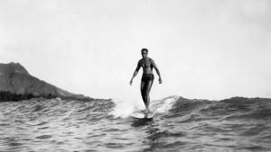 Duke Kahanamoku surfing with Diamond Head at left in the background on Oahu Island in the Hawaiian Islands.