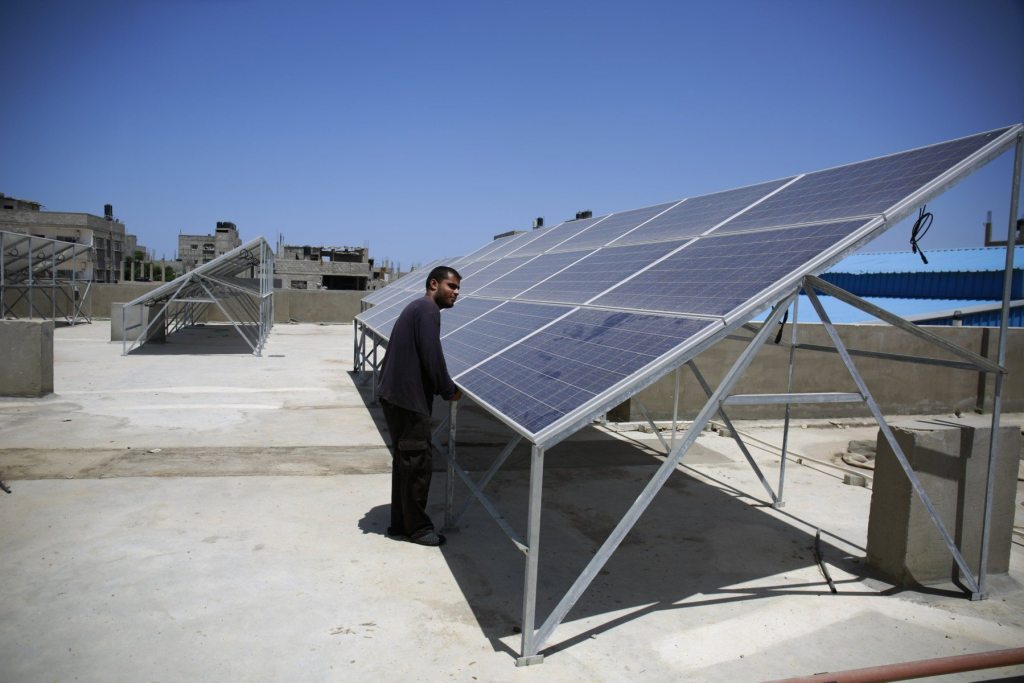 Un habitante de Gaza muestra la pequeña planta de energía solar.