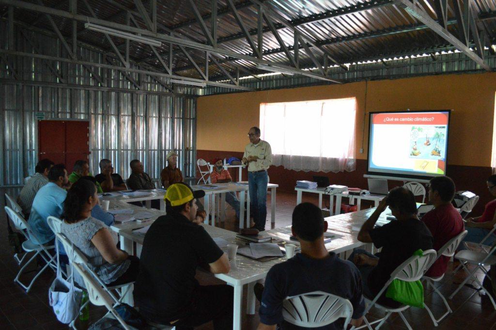 Agricultores atienden la exposición del especialista Elías de Melo, en el Salón Comunal de Llano Bonito de León Cortés, en Costa Rica, durante un taller destinado a capacitarles en la adaptación de sus cafetales al incremento de las temperaturas.