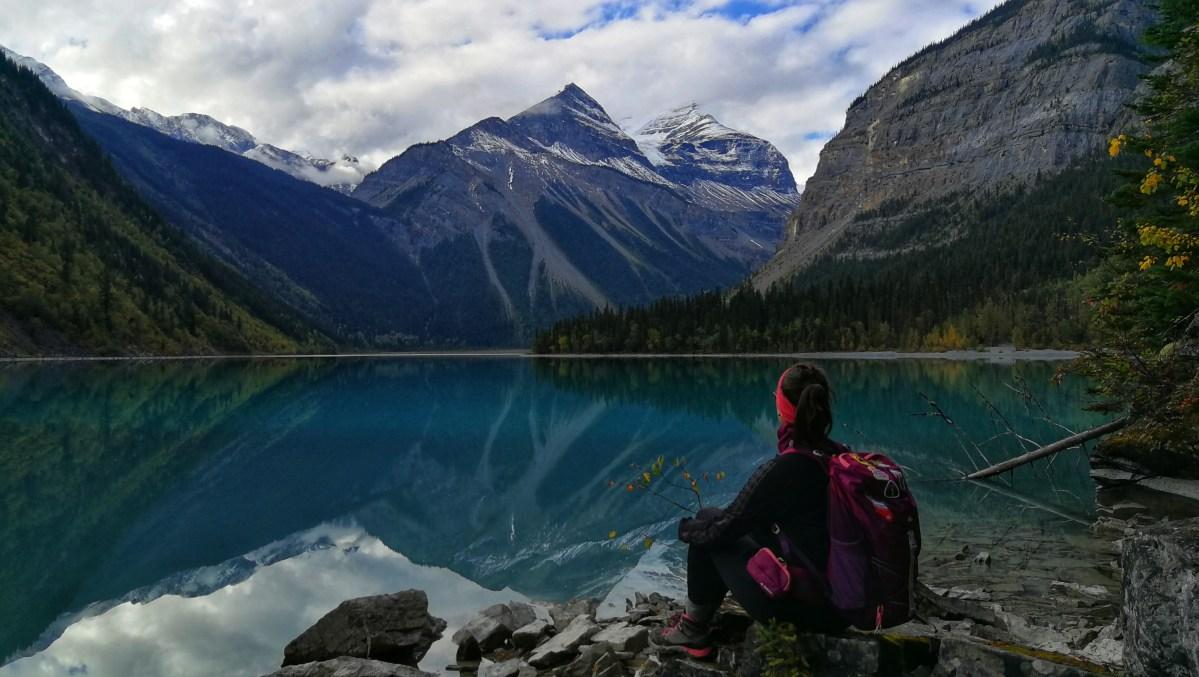 Frau sitzt am Kinney Lake in den Rocky Mountains, Berge im Hintergrund, die sich im Wasser spiegeln