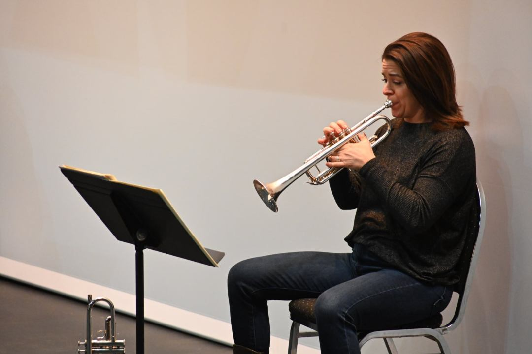 Audrey Patterson playing the trumpet against a white backdrop