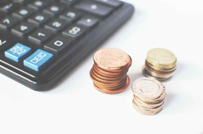 gold colored coins near calculator