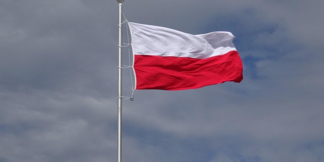 polska flaga powiewa na tle pochmurnego nieba
