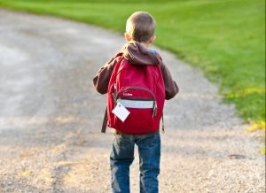 Child with backpack on walking