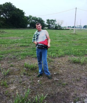 Kody spreading bermudagrass seed on a small pasture.