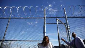 Sheila Devereux walks through a gate opened by Unit Manager Shola Shopeyin at the Oklahoma Department of Corrections in McLoud, Okla. Devereux was sentenced to life in prison without parole after her third felony drug conviction.