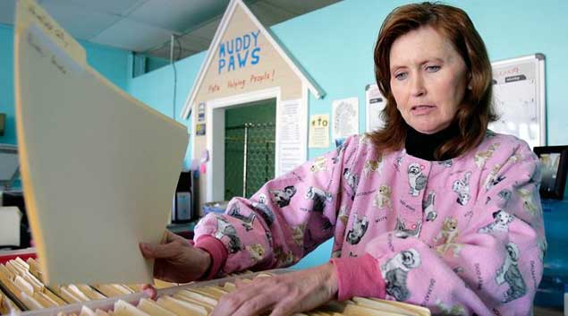 Debbie Davis, a former inmate convicted of embezzelment in both Kansas and Oklahoma, files paperwork at the front desk at Muddy Paws, a pet grooming and boarding shop she now works at in Tulsa, Oklahoma.