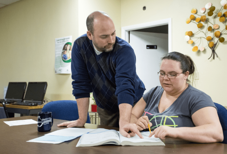 Instructor Joe Haynes (left) helps Brittney Scott with her math homework at the South Tulsa Community House, where Scott is taking GED classes.