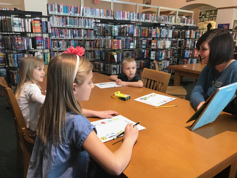 Epic teacher Katie Biswell works with students at the Sapulpa library.