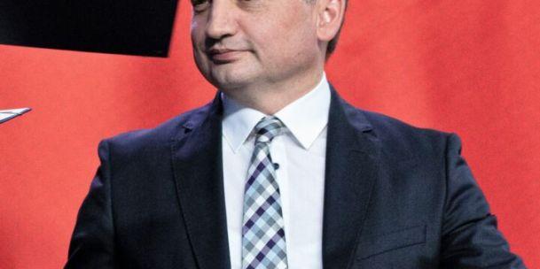 Zbigniew Ziobro siedzi, uśmiechnięty z piórem w ręku