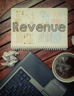 Notebook with text inside Revenue on table with coffee, laptop p