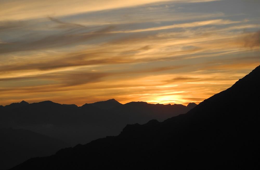 Il cielo, il sole e le nuvole si sono vestiti di colori caldi e stanno danzando lenti. Tramonto al Rifugio de Rabouns (Francia)