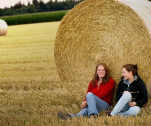 Two Girls sitting in Field with Straw Bales