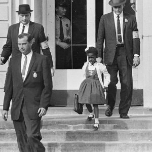 Six-year-old Ruby Bridges being escorted out of school.