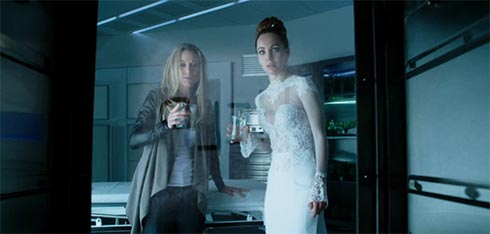 Zoie Palmer and Ksenia Solo watch HELP appear on a glass door