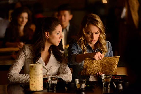 Bo and Tamsin look at a scroll.