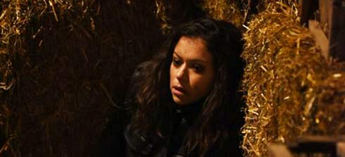 Tatiana Maslany as Sarah hides behind bales of hay