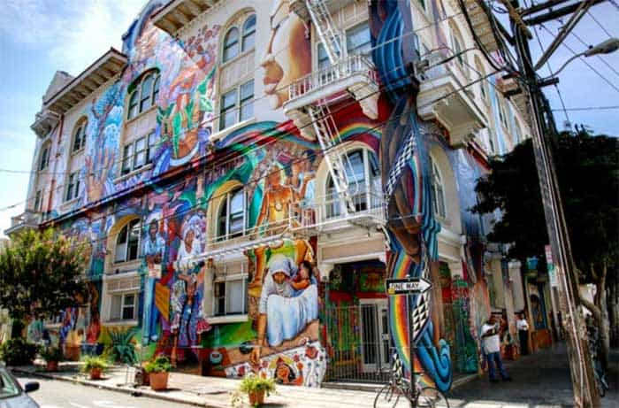 a 3 story building covered with colorful murals