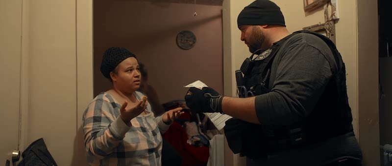 An ICE officer asking to enter a home in Immigration Nation