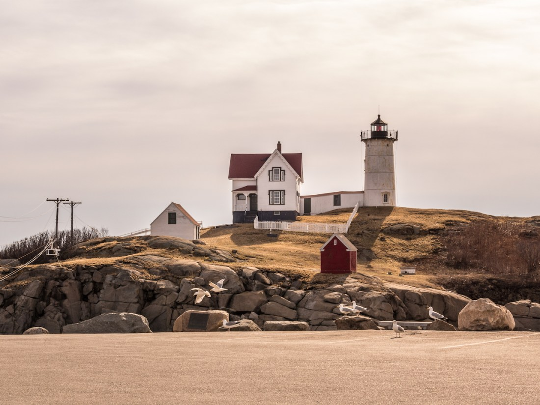 a small white cottage and lighthouse