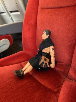 An action figure in a plush red train seat